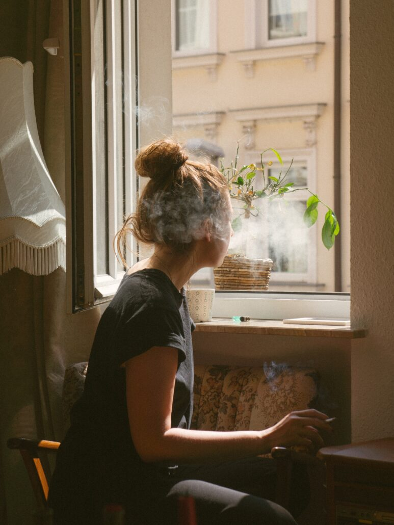 woman smoking weed in Seattle while look through the window