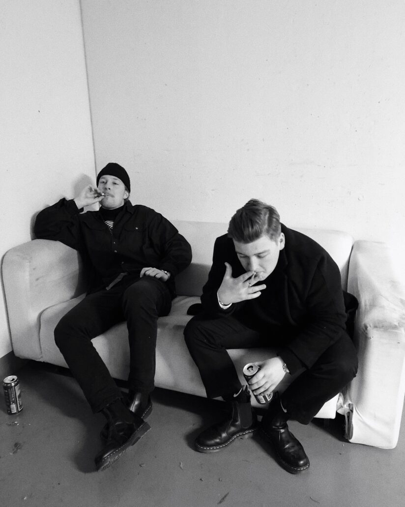 two men sitting on sofa grayscale photo